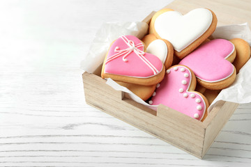 Decorated heart shaped cookies in wooden box on table. Space for text