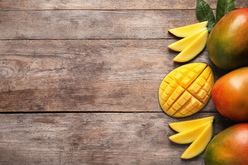 Flat lay composition with mango on wooden background. Space for text