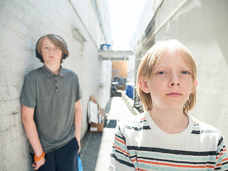 Portrait of brothers standing amidst wall at alley during sunny day