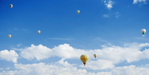 Hot air balloons flying in cloudy sky