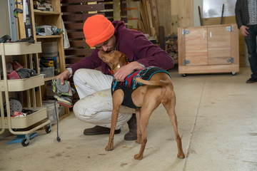 Happy man kissing dog while crouching in workshop