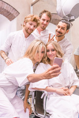 Mother taking selfie with daughter and male hairdressers in hair salon