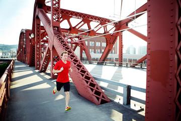 Male athlete running on footbridge in city