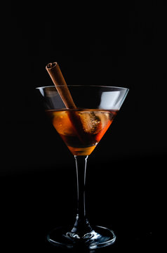 Close up of glass of cocktail with cinnamon stick