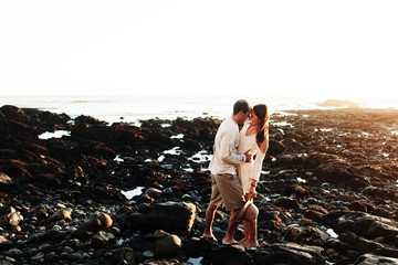 Happy couple romancing while standing on rocks at beach against clear sky during sunset