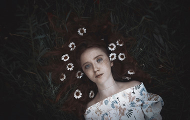 High angle portrait of teenage girl with chamomiles lying on grassy field