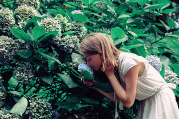 Side view of woman smelling flowers while standing by plants in forest