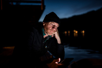 Man using smart phone while sitting at lakeshore against sky in Olympic National Park at night