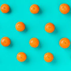 Fruit pattern of fresh mandarin on blue background. Flat lay, top view. Pop art design, creative...