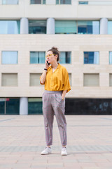 Confident businesswoman talking on smart phone while standing on sidewalk against building in city
