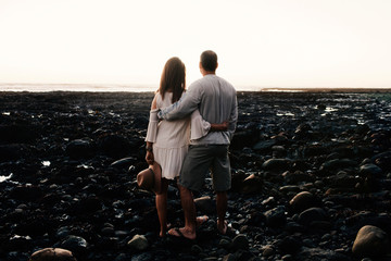 Rear view of couple looking at sea while standing on rocks against clear sky