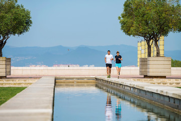 Couple running on retaining wall against clear blue sky at park