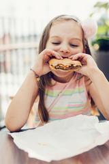 Girl eating burger while sitting at restaurant