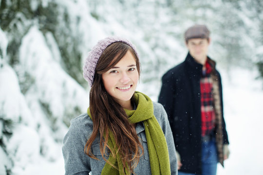 Portrait of girlfriend standing against boyfriend in snow covered forest