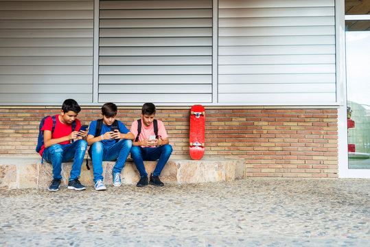 Friends using smart phones while sitting against school building