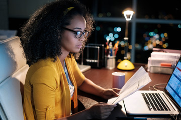 Side view of businesswoman analyzing financial bills while sitting at desk in office