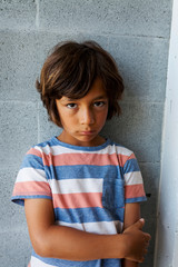 Portrait of serious boy leaning on gray brick wall at home
