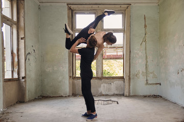 Man lifting ballerina while dancing in old building