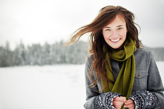 Portrait of smiling woman standing against sky in snow covered forest