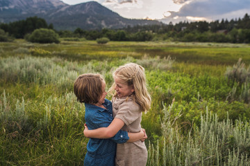 Happy sisters looking at each other while embracing on grassy field in forest during sunset