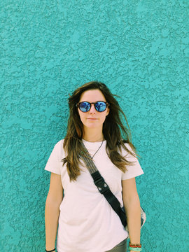 Portrait of confident woman wearing sunglasses while standing against turquoise wall