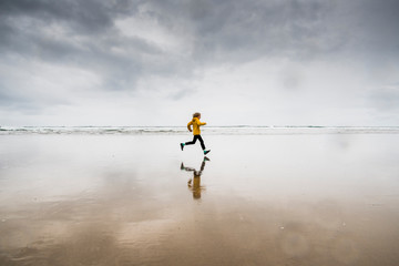 Side view of boy running at beach against cloudy sky