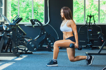 Woman In Fashion Sports Clothes Training, Doing Lunges Exercise with dumbbells in the gym