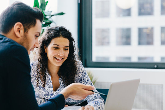 Businessman explaining data to female colleague over laptop computer in office
