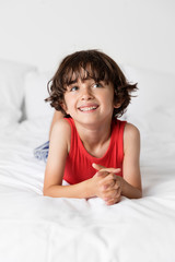 Cute happy boy with hands clasped looking away while relaxing on bed at home