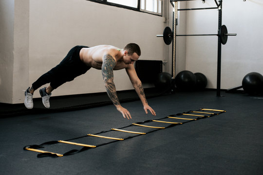 Full length of shirtless young man using agility ladder while warming up in gym