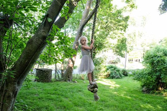 Girl swinging on rope in backyard
