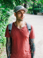 Tattooed man wearing cap looking away while standing by plants in park