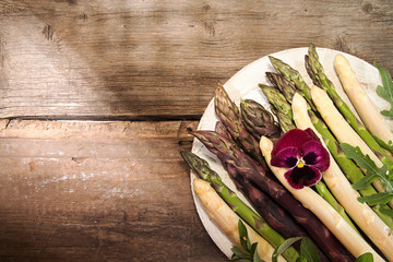 High angle view of various asparagus with flower in plate on wooden table
