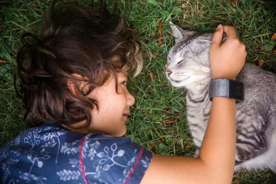 High angle view of boy petting cat while lying on grassy field in yard
