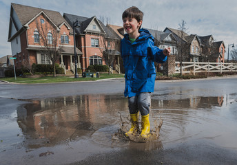 Full length of playful boy wearing rubber boots while jumping in puddle on road against houses