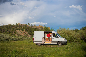 Man standing in motor home against cloudy sky at forest