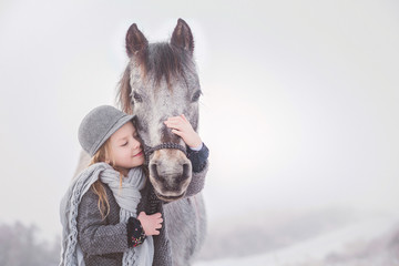 Cute girl embracing pony against sky during winter