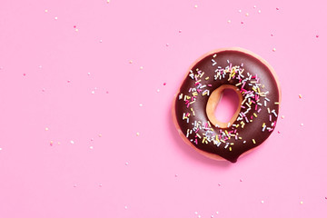 Overhead view of chocolate donut with sprinkles on pink background