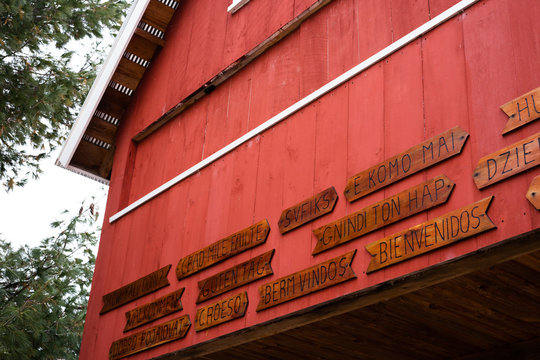 """Saying   """"Welcome"""" in many languages on the side of an old red barn"""