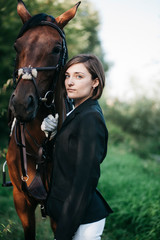Portrait of confident female rider standing with horse on grassy field