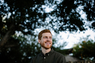 Low angle view of happy thoughtful man looking away while standing against trees at park