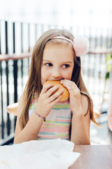 Cute girl looking away while biting burger at restaurant