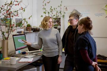 Confident businesswoman explaining to coworkers over desktop computer in workshop