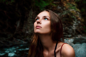 Close-up of thoughtful woman looking away while sitting in forest