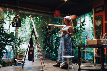 Female artist pointing while looking at painting on canvas in studio