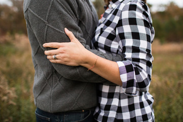 Midsection of romantic couple embracing while standing in forest