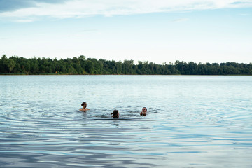 Female friends swimming in lake against sky at forest