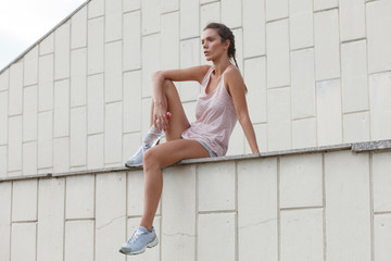 Low angle view of thoughtful woman in sports clothing looking away while sitting on retaining wall