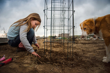 Girl gardening in field with dog against cloudy sky