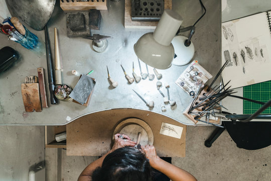 Overhead view of female artisan making jewelry on table in workshop